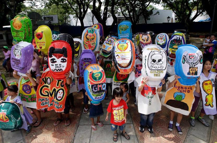 """2013年6月5日,菲律宾奎松城,妇女和儿童高举喷涂过的婴儿洗澡盆,举行示威活动,抗议转基因水稻品种""""黄金大米""""。"""