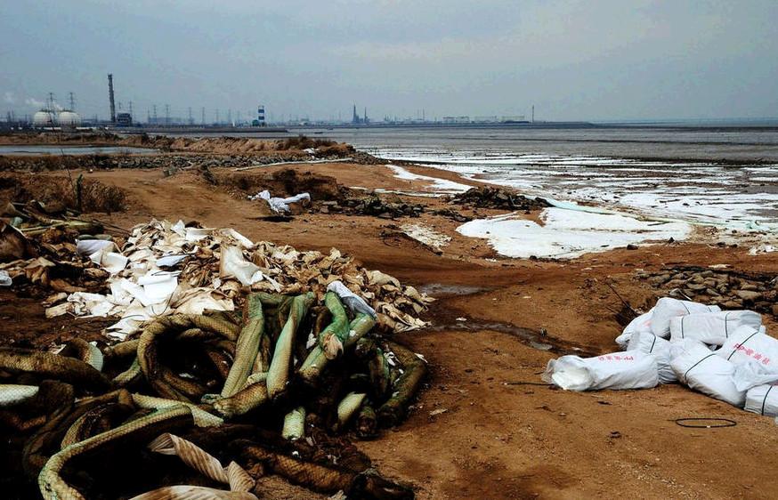 原油海滩上堆放的围油栏和吸油毡