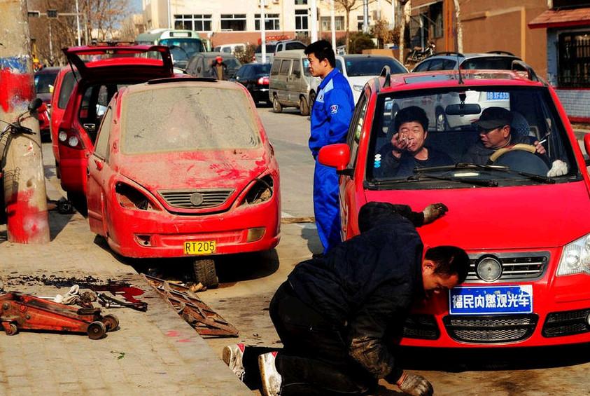 斋堂岛街维修工人在修理爆炸中受损的车辆