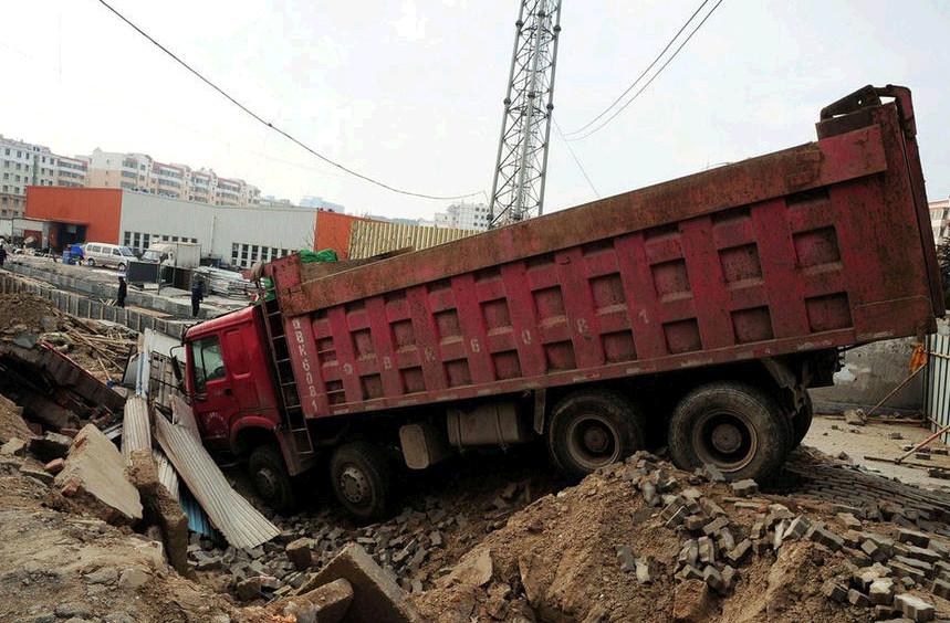 刘公岛路附近一爆炸点一辆受损的货车仍停在爆炸坑里
