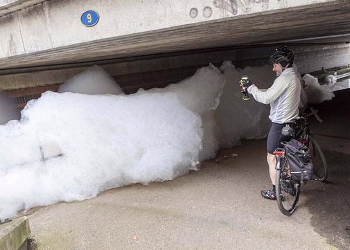 一名骑单车的路人正使用手机给蔓延到车道上的泡沫拍照。英国环境部正介入调查,评估泡沫是否对野生动物产生影响。
