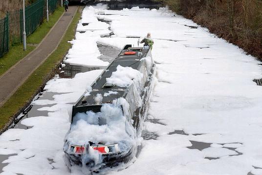 """据英国《每日邮报》4月7日报道,英国曼彻斯特地区的阿什顿运河(Ashton Canal)附近一家化工厂4月5日发生火灾。消防人员灭火时,起火建筑物内储存的洗涤剂与水混合,产生大量泡沫,导致阿什顿运河变成""""泡沫河"""",泡沫墙最高达到1.8米。"""