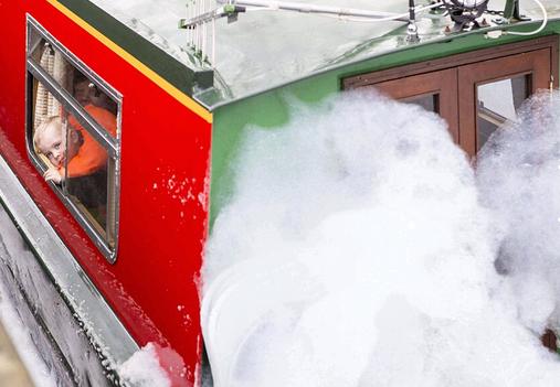这名3岁男孩正透过轮船窗子向外看,他的家人则在设法穿过泡沫区。