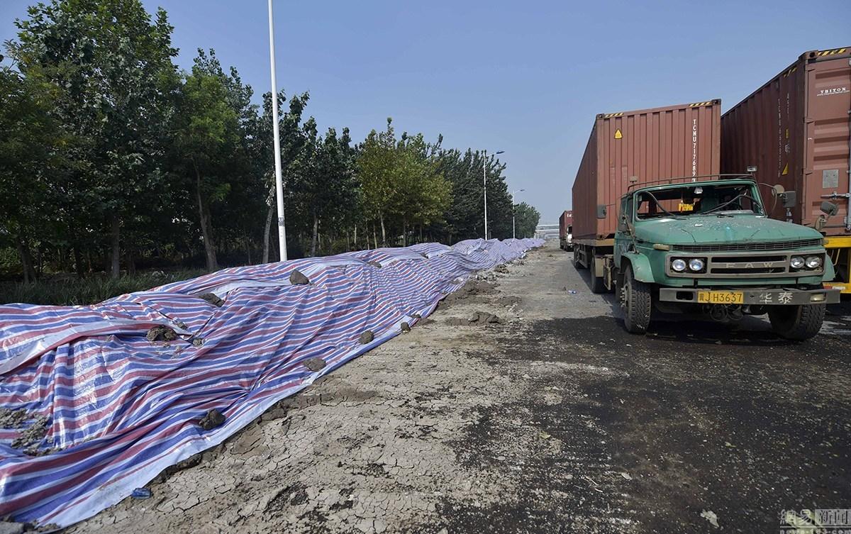 """8月16日,天津港""""8·12""""瑞海公司危险品仓库特别重大火灾爆炸事故现场周围用泥土和塑料布搭建起了一米多高的围挡进行隔离。"""